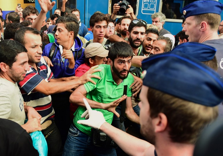 TOPSHOTS Migrants protest at the Eastern (Keleti) railway station of Budapest on September 1, 2015, during the evacuation of the railway station by local police. Budapest's main international railway station ordered an evacuation as hundreds of migrants tried to board trains to Austria and Germany, an AFP reporter at the scene said.  AFP PHOTO / ATTILA KISBENEDEK