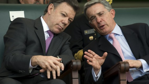 Colombian President-elect Juan Manuel Santos (L) speaks with outgoing President Alvaro Uribe (R) at the handover ceremony of the Colombian Armed Forces supreme command at a military school in Bogota on August 6, 2010, on the eve of his government's inauguration. Colombian admiral Edgar Cely is taking over as head of the Armed Forces. AFP PHOTO/Eitan Abramovich