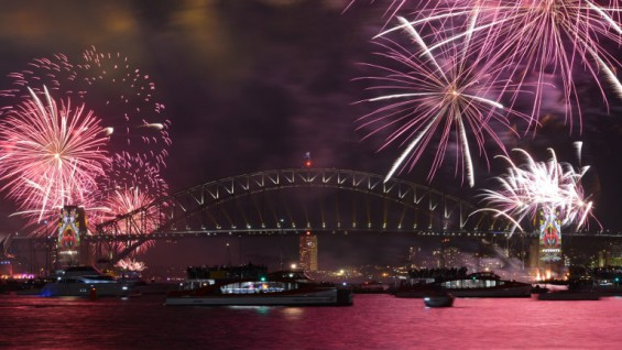 New Year's Eve fireworks illuminate Sydney's iconic Harbour Bridge during the traditional early family fireworks show held before the main midnight event on December 31, 2015.   AFP PHOTO / Peter PARKS / AFP / PETER PARKS